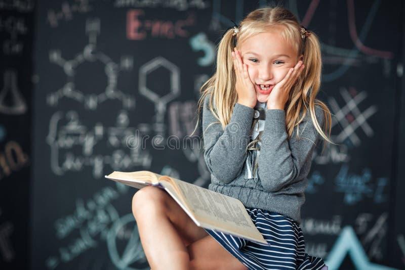 Una scolara bionda dolce della ragazza si siede su una lavagna con il fondo di formule della scuola Compito degli impianti leggen fotografia stock