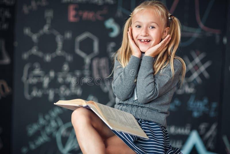 Una scolara bionda dolce della ragazza si siede su una lavagna con il fondo di formule della scuola Compito degli impianti leggen immagine stock