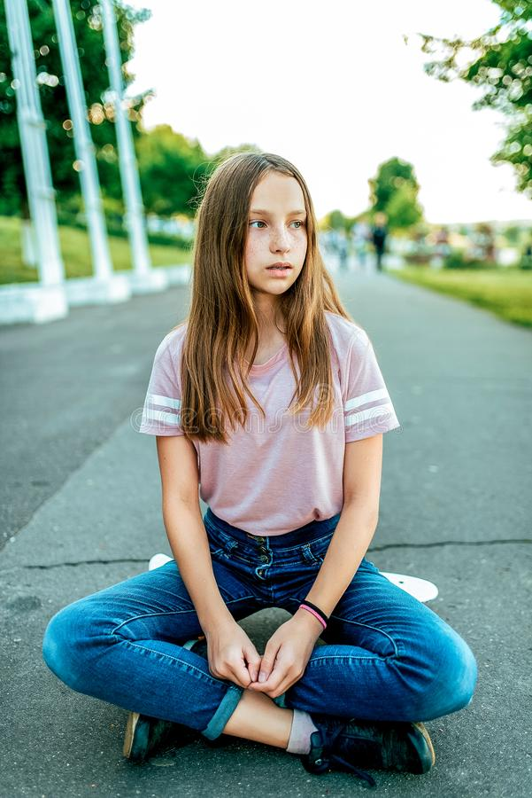 Una scolara della bambina di 12-16 anni, sulla via si siede il pattino di estate in parco Riposando dopo la camminata e fotografie stock