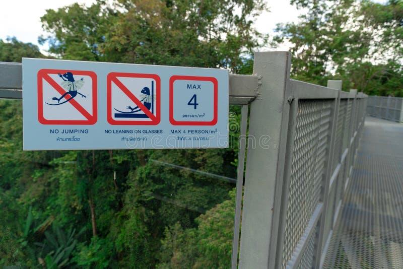 Una señal de peligro en la calzada del toldo en un jardín botánico foto de archivo libre de regalías