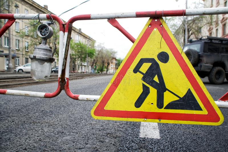 Una señal de tráfico advierte de la construcción realizada en una calle de la ciudad Cerca y linterna temporales Econom?a urbana imágenes de archivo libres de regalías