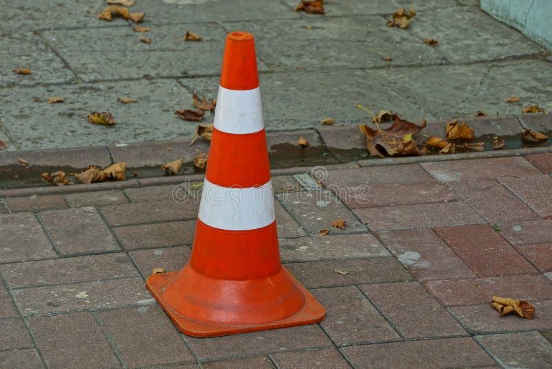 Una señal de tráfico de un cono plástico rayado se coloca en la acera en la calle imagenes de archivo