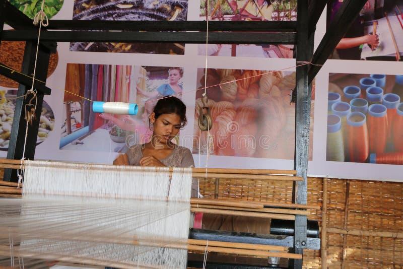 Una señora camboyana weavering las bufandas de seda imagen de archivo libre de regalías
