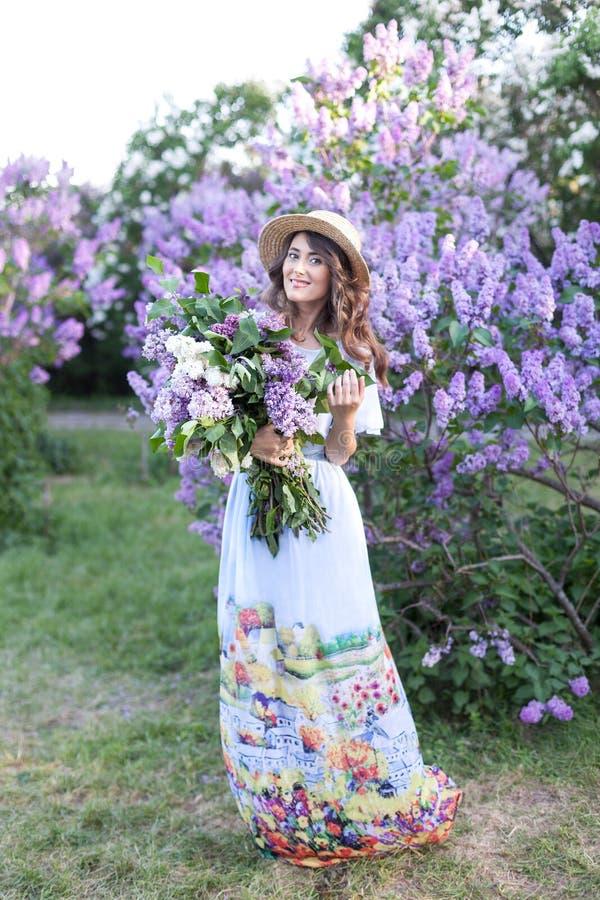 Una señora en un vestido largo elegante, en un sombrero de paja y un peinado aseado se está colocando en un jardín del verano Una imagenes de archivo