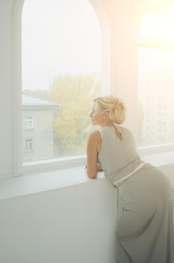Una señora hermosa de 40 años en un vestido de noche largo mira hacia fuera la ventana Tono en el estilo de instagram Puesta del  fotografía de archivo libre de regalías