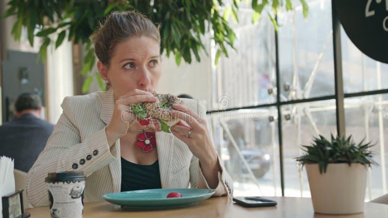 Una señora joven Eating Sandwich en el café foto de archivo