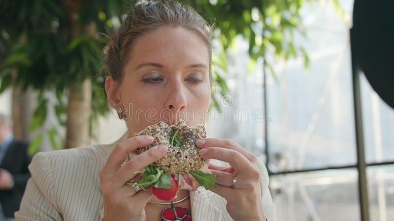 Una señora joven Eating Sandwich en el café imagen de archivo libre de regalías