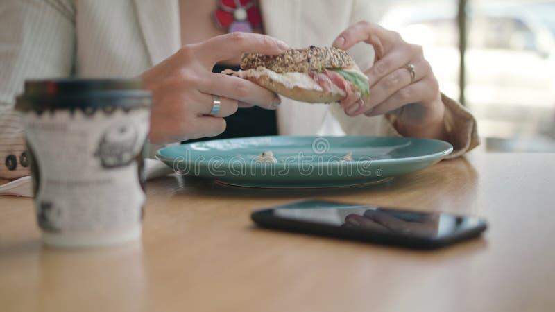 Una señora joven Eating Sandwich en el café fotos de archivo
