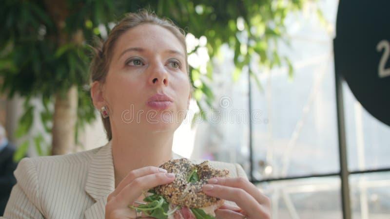 Una señora joven Eating Sandwich en el café imagenes de archivo