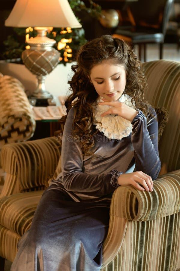 una señora joven medieval se sienta en una silla antigua acogedora del sofá en ojos abatidos pasados de moda de un interior modes fotografía de archivo