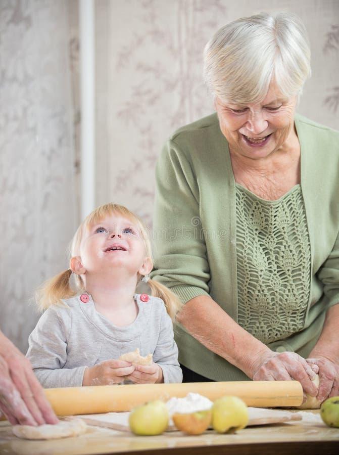 Una señora mayor que hace las pequeñas empanadas con una niña feliz La muchacha que mira para arriba imágenes de archivo libres de regalías