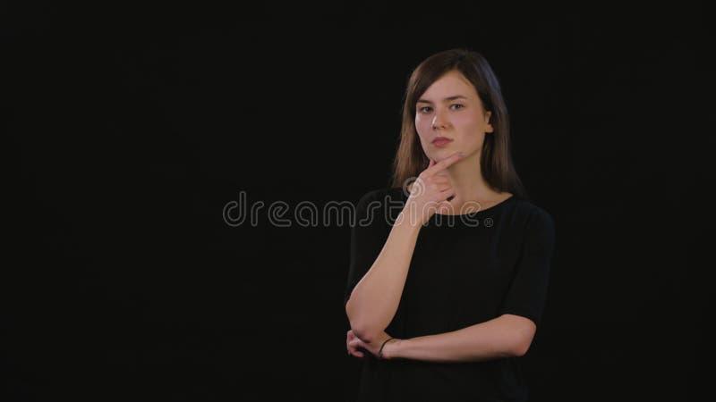 Una señora Mimicing Against un fondo negro fotografía de archivo