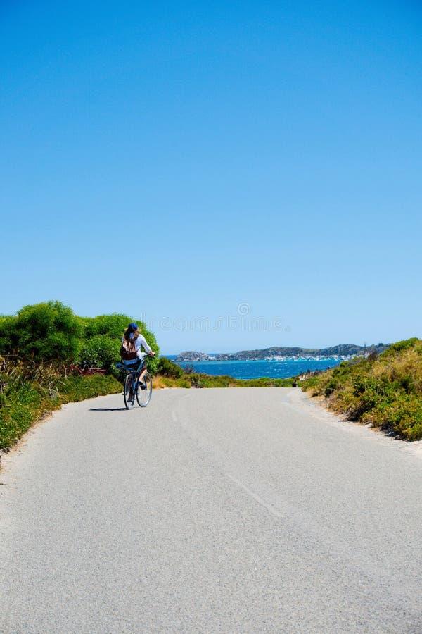 Una señora que completa un ciclo en una isla que pasa por alto el mar foto de archivo libre de regalías