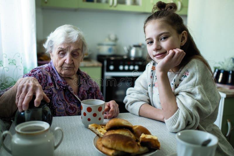 Una se?ora mayor trata un desayuno de la ni?a, sent?ndose en la tabla en su casa fotos de archivo libres de regalías