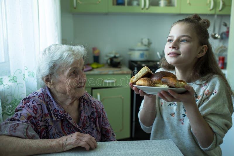 Una se?ora mayor trata un desayuno de la ni?a, sent?ndose en la tabla en su casa fotos de archivo