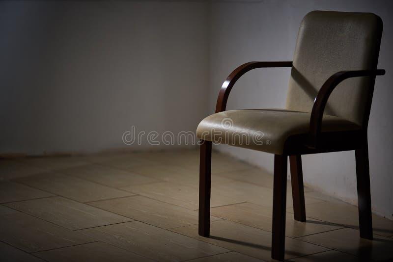 Una sedia moderna vuota in una stanza scura fotografie stock libere da diritti