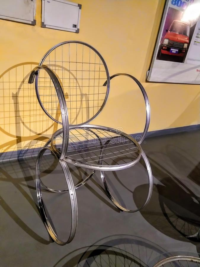 Una sedia a rotelle fatta delle ruote di bicicletta Un concetto unico di ricicla o riutilizza immagini stock