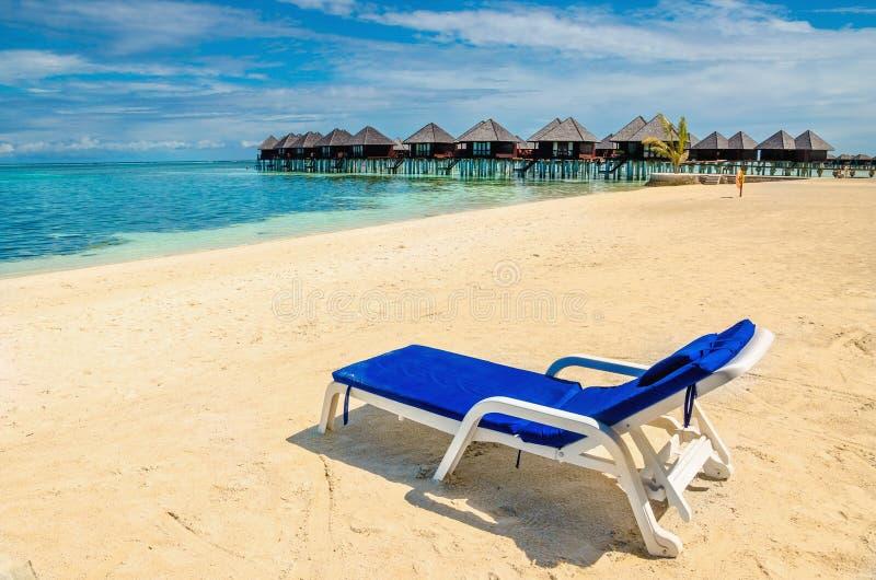 Una sedia a sdraio blu sui precedenti delle capanne esotiche sull'acqua fotografia stock libera da diritti