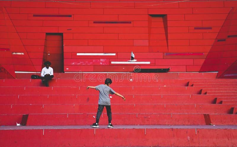 Una seduta e una lettura dell'uomo un libro e un giovane ragazzo sta camminando sopra fotografie stock libere da diritti