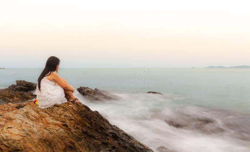 Una seduta triste e depressa della donna fotografia stock