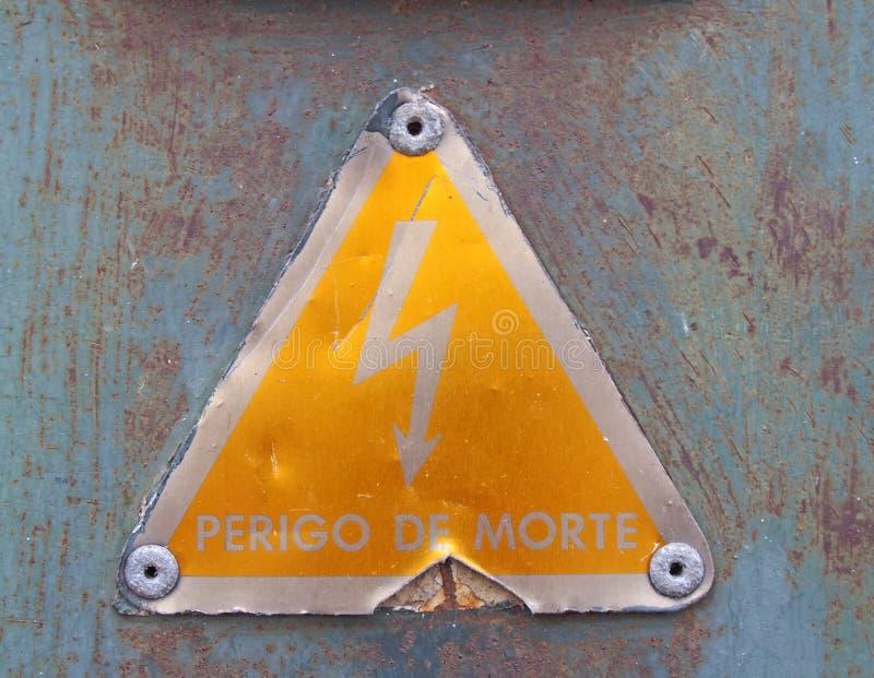 una segnaletica di sicurezza portoghese gialla triangolare di elettricità del vecchio metallo con un simbolo audace reading perig immagine stock libera da diritti