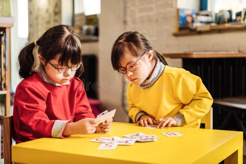 Una sensibilità soleggiata di due bambini in questione nell'esame imparante le carte fotografie stock