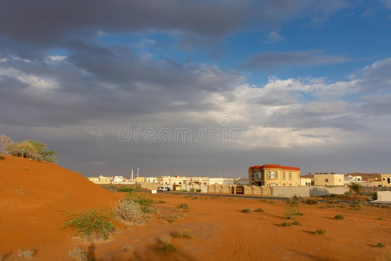 Una sera tempestosa nei UAE con le nuvole ed il cielo blu scuri sopra la città e le dune di sabbia arancio fotografia stock