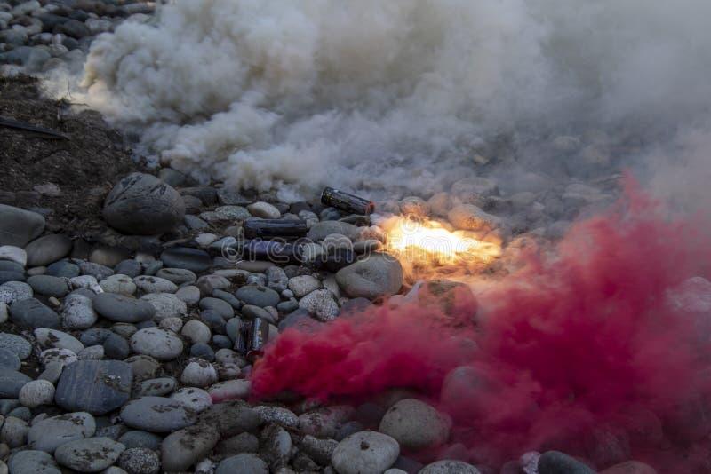 Una serie di bombe fumogene che mettono sulla terra rocciosa fotografia stock libera da diritti