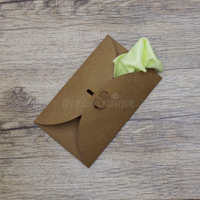 Una servilleta verde clara se pega fuera del sobre del arte Visión superior imagen de archivo libre de regalías