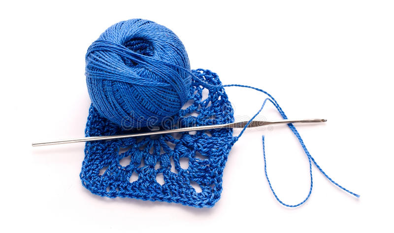 Una sfera di filato blu con il patt del crochet e di lavoro a maglia immagini stock libere da diritti