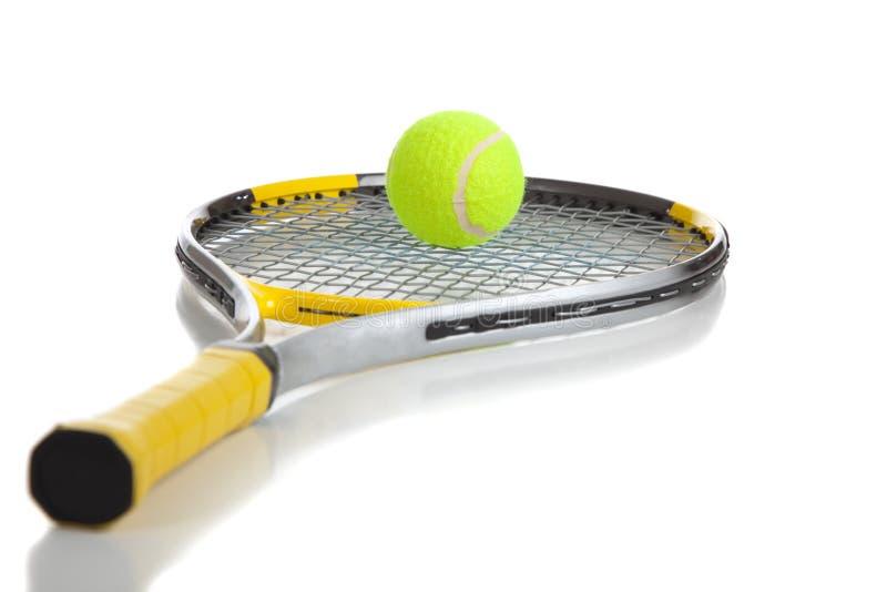 Una sfera e una racchetta di tennis su bianco immagini stock libere da diritti