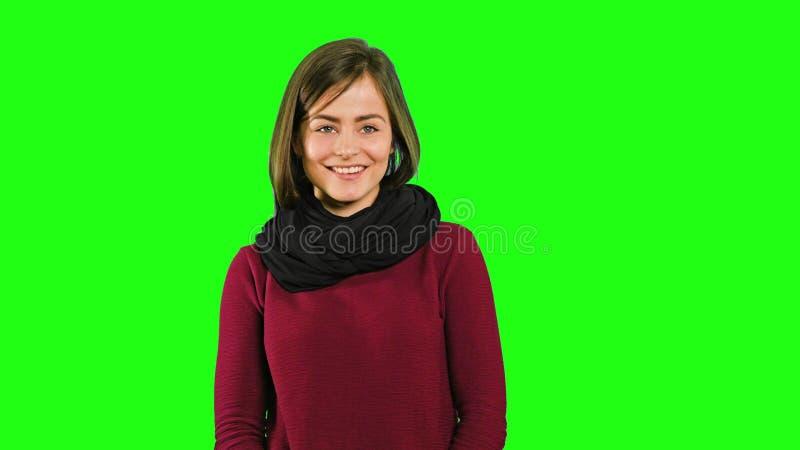 Una signora amichevole Smiling contro un fondo verde fotografie stock libere da diritti