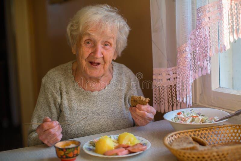 Una signora anziana cena la seduta alla tavola immagini stock