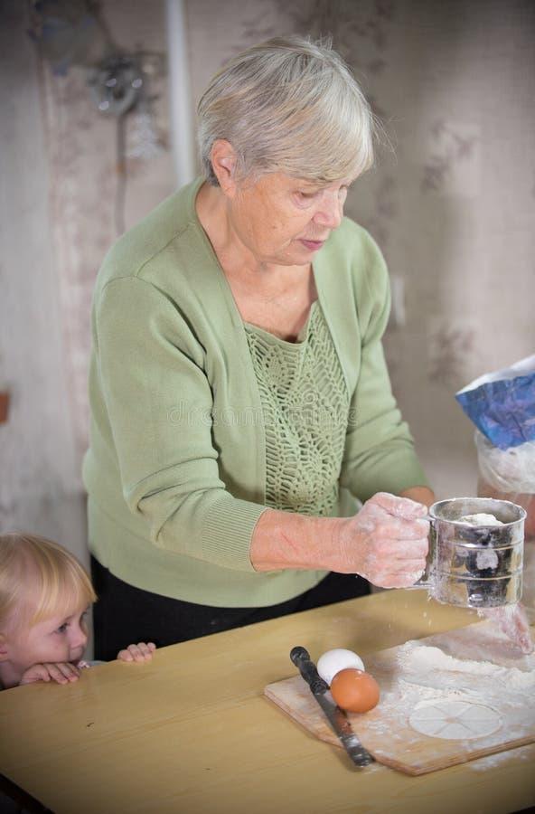 Una signora anziana che produce le piccole torte con la bambina Impasti la pasta immagine stock libera da diritti