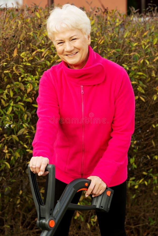 Una signora felice anziana che falcia nel giardino. immagine stock