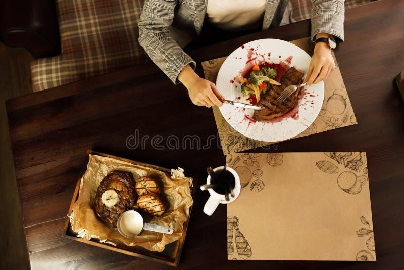 Una signora solida si siede ad una tavola in un ristorante lussuoso fotografia stock
