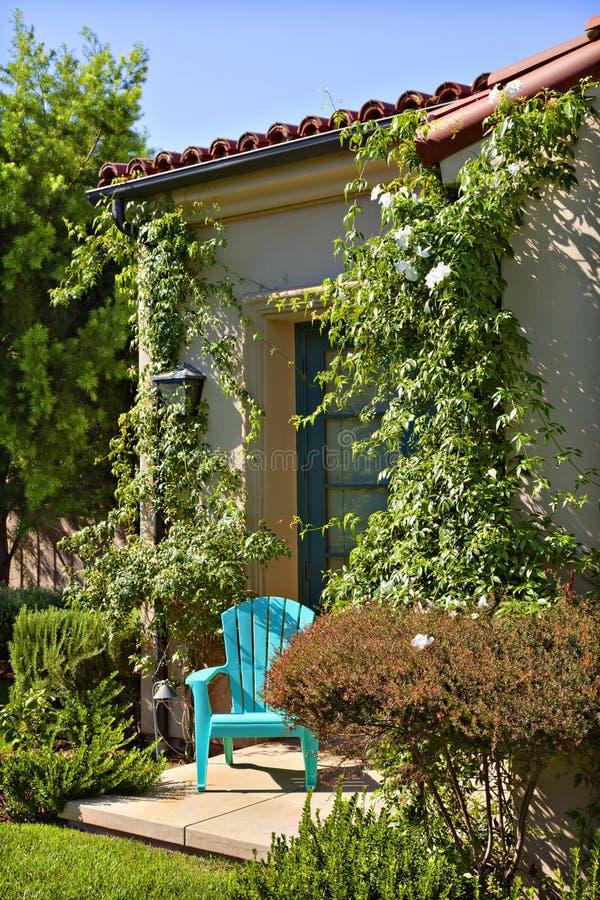 Una silla azul sola fuera de una casa rodeada por las plantas imagen de archivo