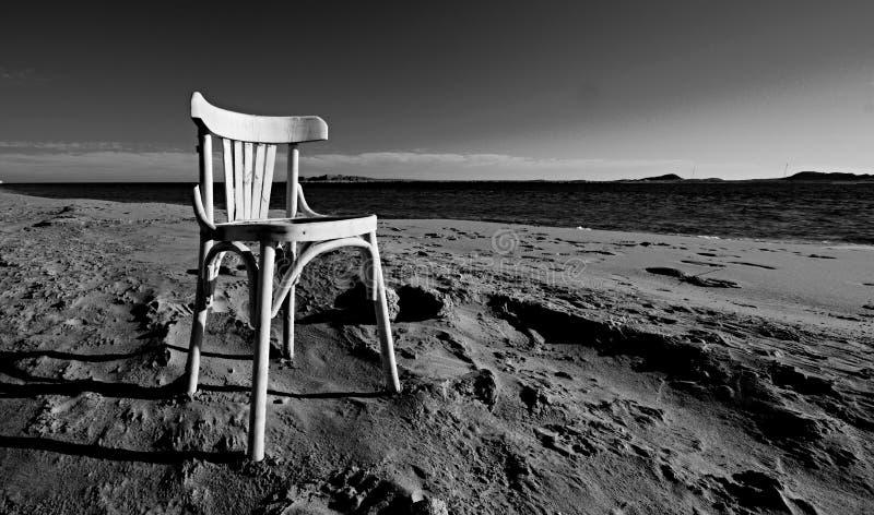 Una silla blanca vieja vacía en una playa arenosa el Mar Rojo fotos de archivo