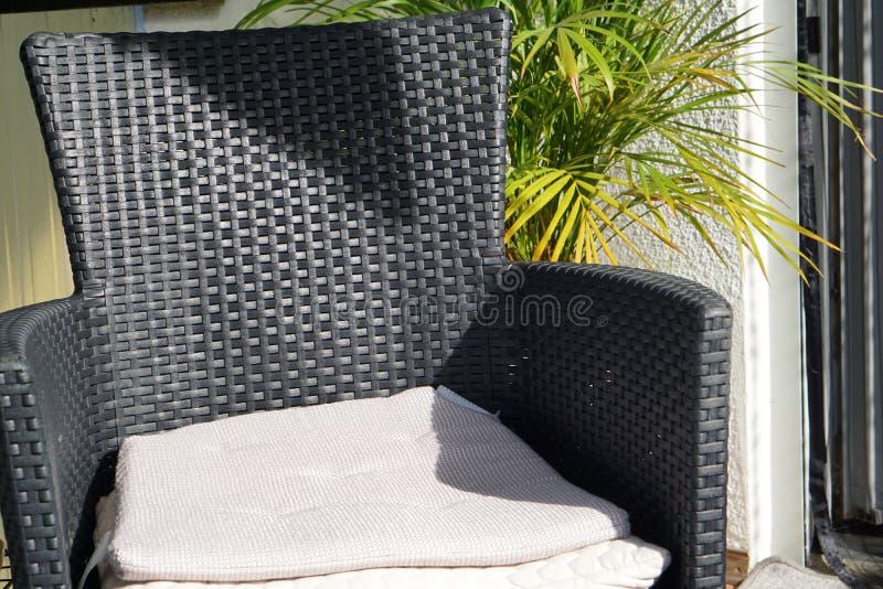 Una silla con los cojines al aire libre en el jardín o el balcón delante de una planta verde imagen de archivo