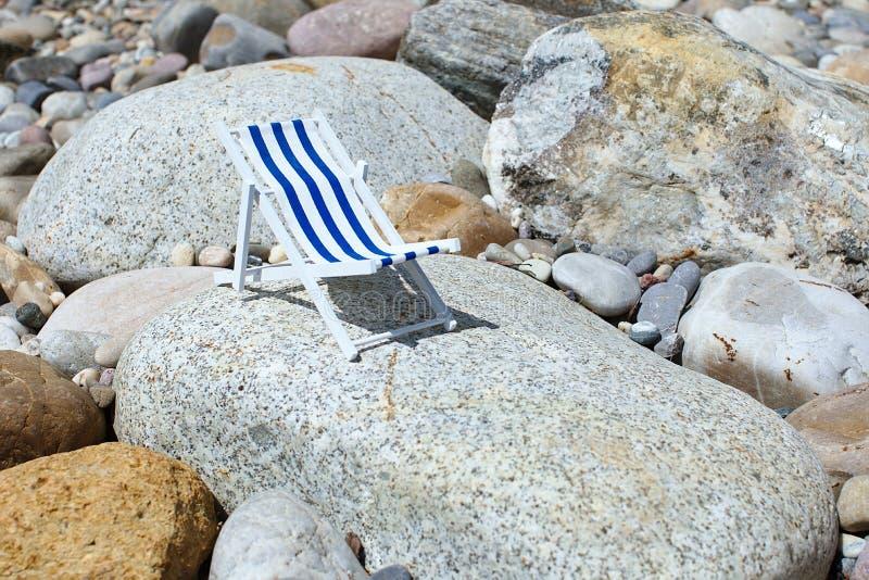Una silla de playa rayada del juguete para los soportes que toman el sol y de relajaciones en una piedra grande en un día soleado imagen de archivo libre de regalías