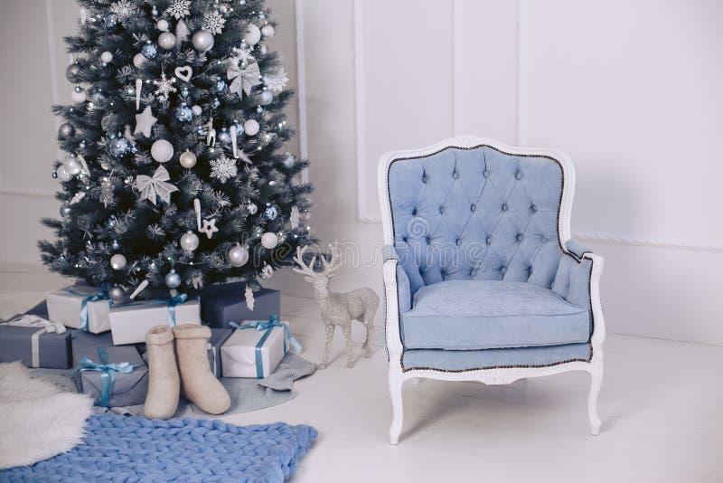 Una silla elegante moderna azul en el interior del ` s del Año Nuevo Árbol de navidad con las decoraciones Regalos en paquetes imagen de archivo