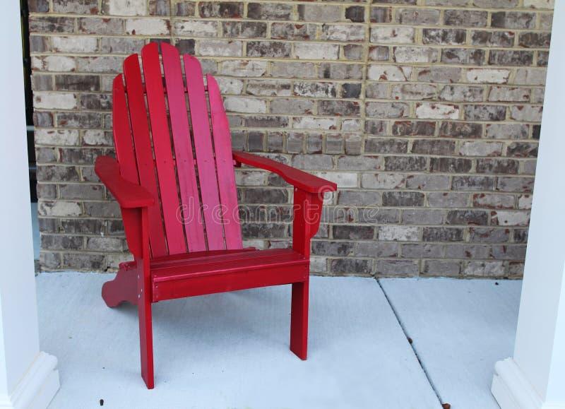 Una silla roja de madera en un p rche de entrada imagen de - Sillas de porche ...