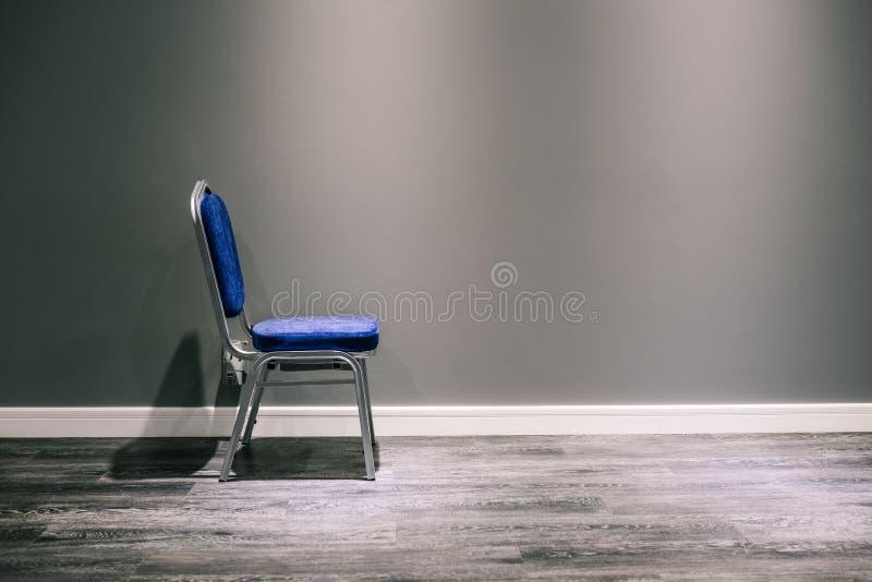 Una silla sola con las piernas de plata en azul Se coloca en la pared gris En la parte inferior de un rodapié y de una lamina bla fotos de archivo