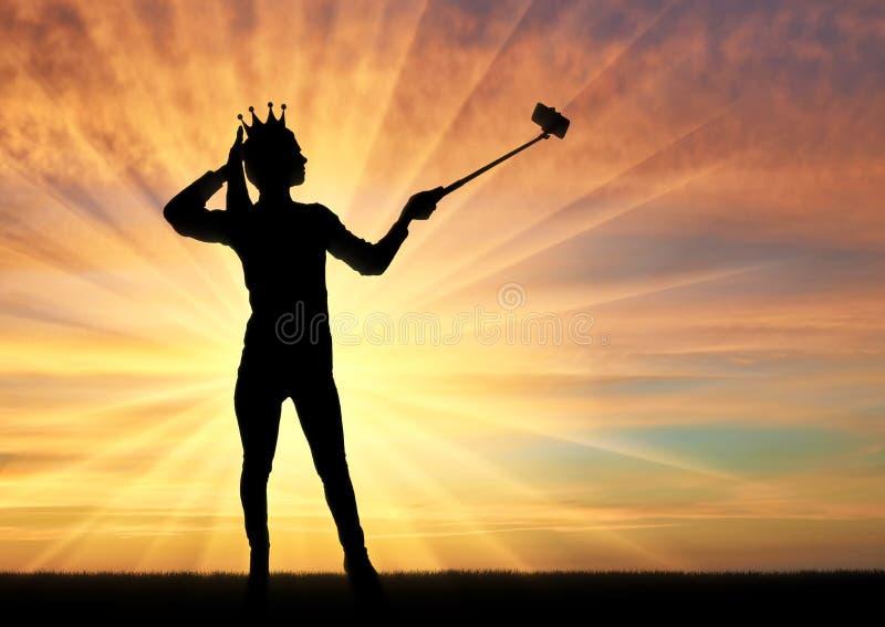 Una silueta de una mujer narcisista y egoísta con una corona en su cabeza, hace el selfie en el teléfono foto de archivo
