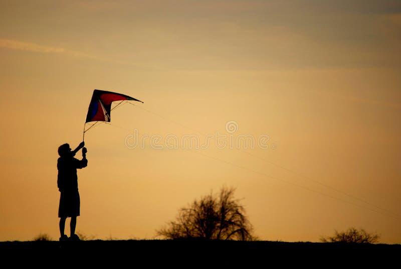 Una silueta de un adolescente que sostiene una cometa en fondo anaranjado fotos de archivo libres de regalías