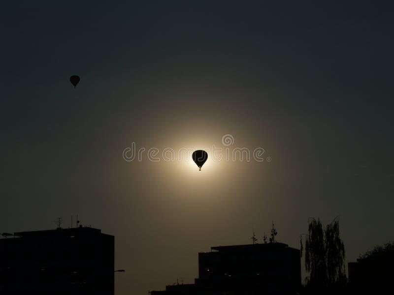 Una silueta de un globo en el medio del sol con las siluetas del suburbio, día Hradec Kralove del globo fotografía de archivo
