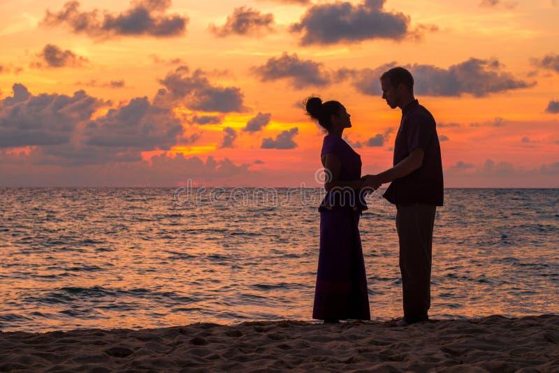 Una silueta de un hombre y de una mujer que llevan a cabo las manos en la puesta del sol en la playa fotos de archivo