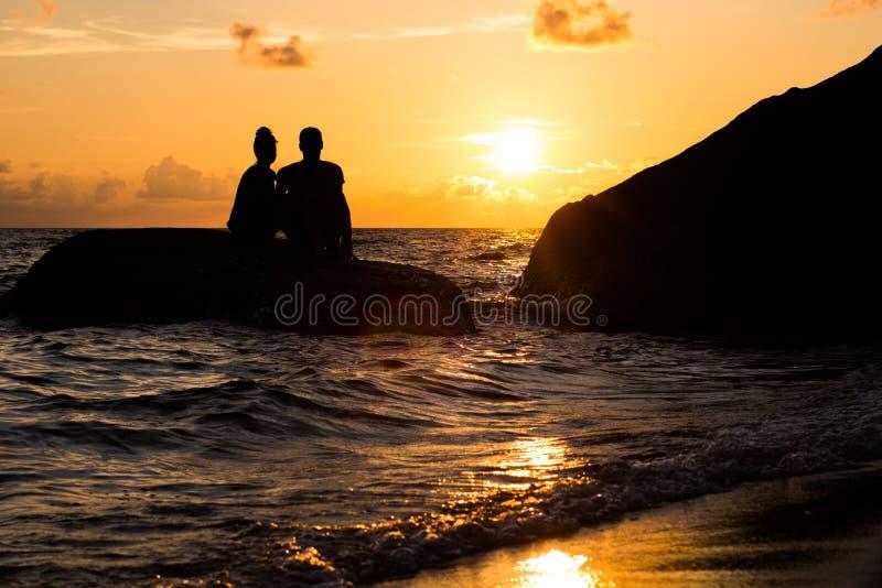 Una silueta de un hombre y de una mujer que se sientan junto en la puesta del sol en una roca en el océano foto de archivo libre de regalías