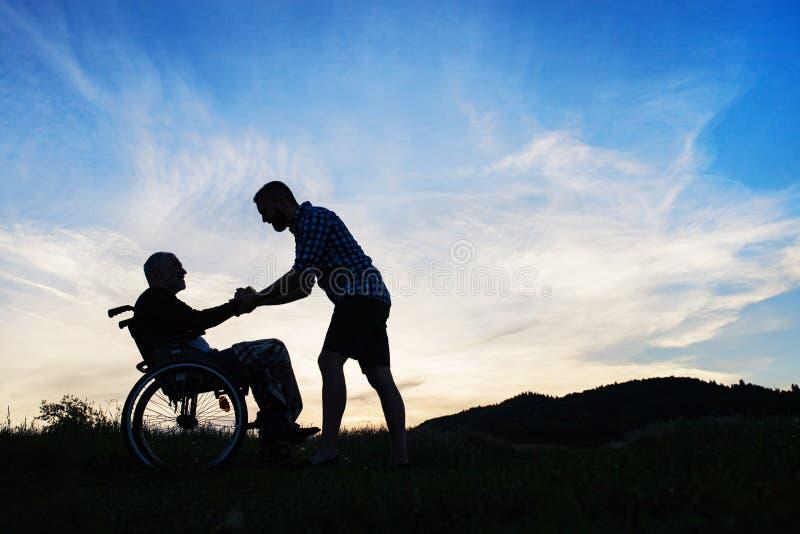 Una silueta del hijo adulto que mira a su padre en silla de ruedas en naturaleza la puesta del sol imagen de archivo libre de regalías