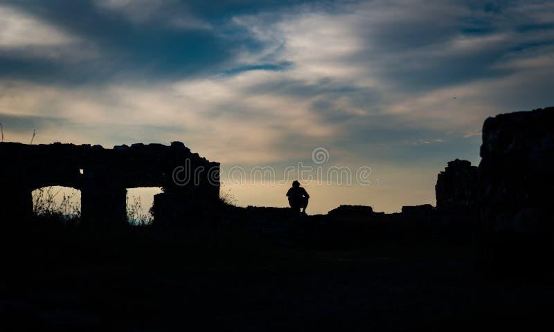 Una silueta del hombre que se sienta al borde de un castillo arruinado fotografía de archivo libre de regalías